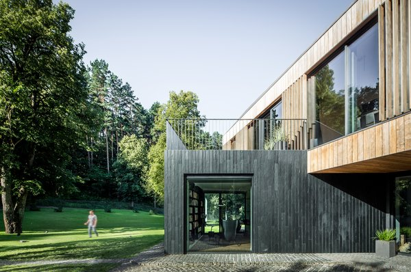 """The vertical orientation of the exterior siding is meant to mimic the surrounding tree trunks in the natural setting. The wood siding was sourced from Kebony, """"which modifies sustainably sourced softwoods by heating the wood with furfuryl alcohol—an agricultural byproduct,"""" says the company. Doing so enables the softwoods to """"permanently take on the attributes of tropical hardwood,"""" relaying all the benefits of tropical hardwoods without relying on deforestation practices. The granite patio nods to traditional farmhouse foundations."""