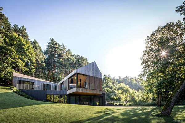 An Updated Farmhouse in Lithuania Cantilevers Over a Parkland Setting