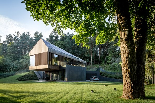 """""""The ground floor is partly hidden in the slope,"""" say the architects, so as to make it seem as though it is receding into the landscape. The cantilevered volume houses the living room and creates protected space below for an outdoor patio."""