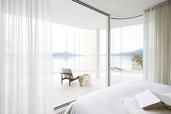 The bedroom all but merges with the landscape thanks to frameless sliding glass doors from Sky-Frame.