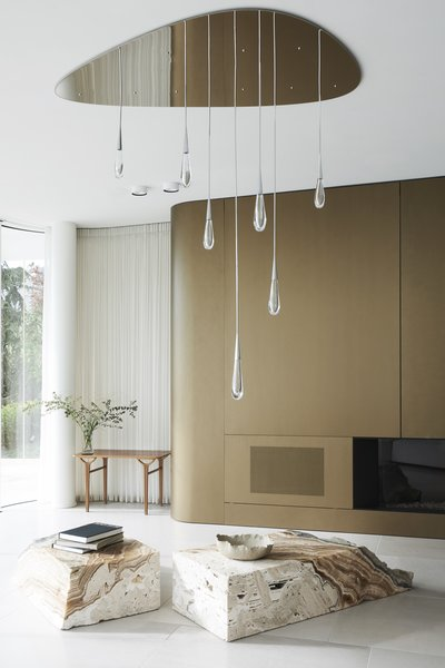 A Brushed Brass Fireplace Surround Subtly Repeats The Architectural Curves.  The Bespoke Ceiling Fixture Is