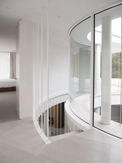 The staircase is suspended on steel rods and borders the atrium, in order to bring plentiful natural light into the stair volume.