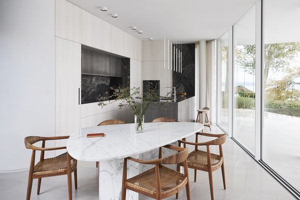 In the kitchen, Hans Wegner chairs surround a vintage triangular marble dining table from Willy Ballez. The island pendants are by Davide Groppi, and the kitchen system is Rossana, an Italian luxury kitchen brand.