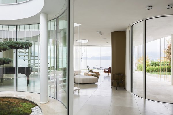 Villa Mosca Bianca by Design Haus Liberty unfolds in layers, its outdoor terraces cascading down to the waters of Lake Maggiore. Frameless sliding glass doors and curving panels of glass connect the interior to outdoor terraces, their shapes echoing the forms of the house and stepping down to the water's edge. Curving glass walls blur the boundary between inside and out, with the meditative views of the lake prioritized. A light palette of natural stone finishes is calming, textural, and leads attention outward.