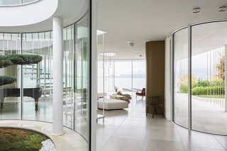 Curving glass walls blur the boundary between inside and out, with the meditative views of the lake prioritized. A light palette of natural stone finishes is calming, textural, and leads attention outward.
