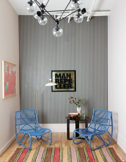 Blue rattan chairs and striped wallpaper greet visitors in the reception area. The artwork (on the left wall) is by Amber Vittoria.