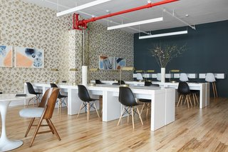 The open work area offers a variety of work stations. White Donald Desks from Bed Bath & Beyond were lined up back to back, and paired with contrasting black Modway Pyramid Dining Side Chairs, also from Bed Bath & Beyond.