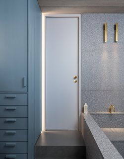 The bathroom can be accessed from the entry side of the apartment, as well as the bedroom via this door. Custom lighting is from PSLab.