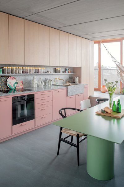 In the kitchen area, dusty pink cabinets are topped with a terrazzo counter and backsplash with integrated shelf. Gold accents, via the canisters, flatware, and faucet, lend a little glam.