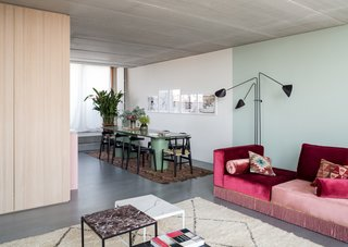 In the dining area, the color of the table, the 'Memphis Melon' by Ester Bruzkus at Studio Coucou, echoes the living room wall paint.