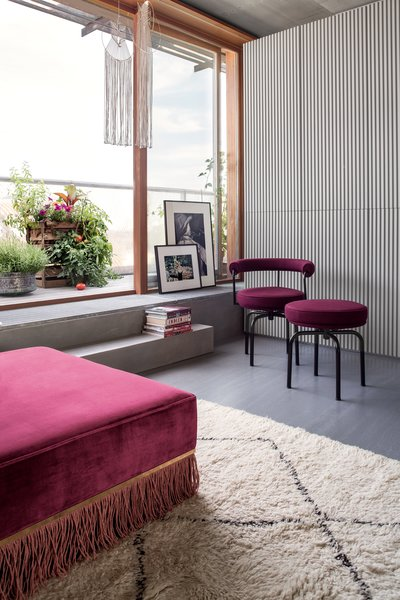 Outdoor spaces bookend the apartment. Totaling 754 square feet, they nearly double the interior area. A custom upholstered LC7 Swivel Chair and LC8 Swivel Stool, designed by Le Corbusier, Pierre Jeanneret, and Charlotte Perriand, occupy a corner of the living room.