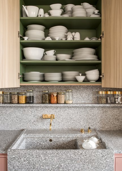 Melon-colored shelves, loaded with vintage dishes, hide inside bleached oak cabinets.