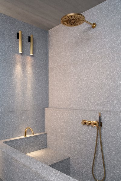 Terrazzo clads the shower and bath. All of the brass faucets in the apartment are from Vola.