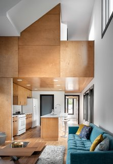 Double-height ceilings increase the sense of space in the living room. For continuity, the maple plywood was used for the kitchen cabinets and ceiling, as well as an accent wall.