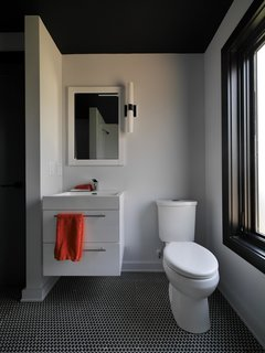 In the bathroom, a wall-mounted vanity saves floor space, and charcoal penny tiles sync with the dark-hued trim found throughout the house.