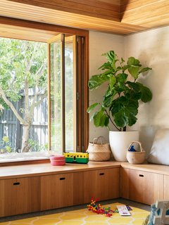 Large windows can be stepped through and connect the new living spaces with the backyard. Built-in bench seats provide convenient storage.