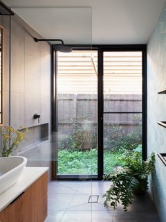 In the master suite bathroom, floor-to-ceiling glass connects the shower to a private side yard.