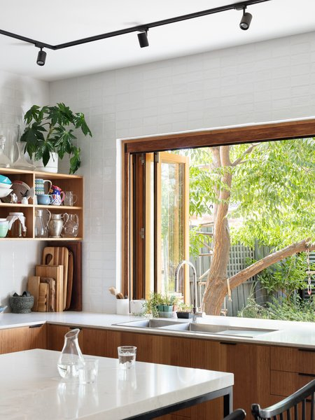 Gardiner Architecture ensured that flexibility, practicality, comfort, and spaciousness were all present in Elm Street House, as well as natural connections to the oft-used backyard and the surrounding neighborhood. The kitchen units are composed of blackbutt veneer and have a matte finish; the counters are Caesarstone. A pass-through window at the sink connects to the yard and makes for easy entertaining.