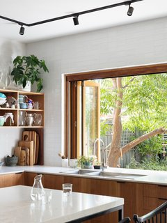 A pass-through window at the sink connects to the yard and makes for easy entertaining.