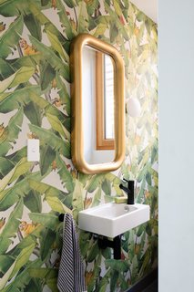The powder room features Botanica Jungle Fever wallpaper by Emily Ziz.