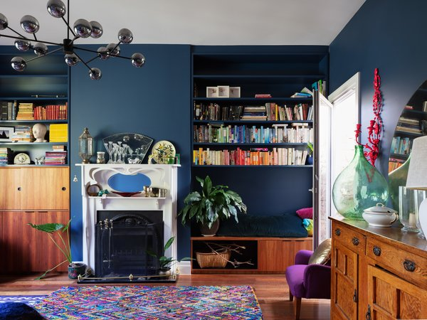 The existing living room received modern built-in storage and blue paint that syncs with the addition.