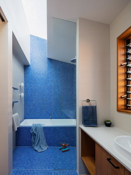 Brilliant blue tile from Classic Ceramics cascades down the wall, wraps the tub, and covers the floor in the kids' bath.