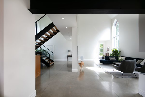 The altar-end of the building was also enclosed to form the boundary for the living room, with the attached office and workshop behind the wall on the lower level.  The upper level walkway to the master suite provides a sense of definition in the expansive space, which is 28 feet high at its peak.