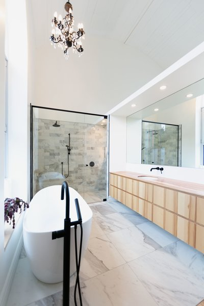 In the master bathroom, the scheme recalls the kitchen finishes, with a vanity custom-built out of natural Ashwood by Ébénisterie Gaston Chouinard.