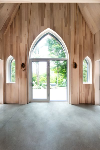 After: Now, vertical strips of wood from American tulip trees accentuate the height of the entry wall and surrounds the new backyard access, with glass that mimics the window shapes on either side. The ropes are in place to ring the bell in the tower.