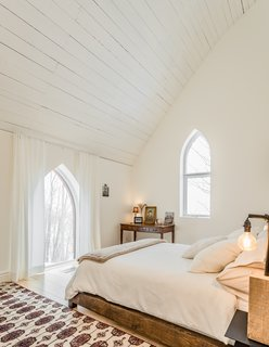 White paint in the guest room highlights the arched windows and original vaulted ceiling.