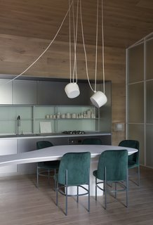 "In the kitchen/dining room, a mint backsplash syncs with emerald Etel ""AL"" chairs. The ceiling light is the Aim by FLOS."