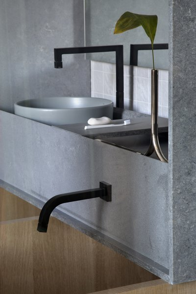 Rugged concrete stone by Caesarstone forms the bathroom counter and sinks, and hovers over the soaking tub.