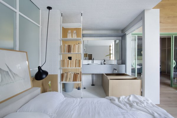 "The bookshelf separating the bedroom and bathroom is the ""Icon"" system from ""Sollos"" by Brazilian designer Jader Almeida."