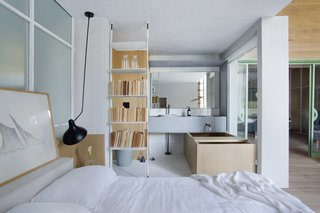 """The bookshelf separating the bedroom and bathroom is the """"Icon"""" system from """"Sollos"""" by Brazilian designer Jader Almeida"""
