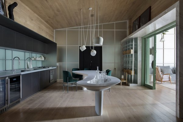 """A marble """"portal"""" breaks up the wood finishes and lowers the ceiling around the passageway between the living room and kitchen/dining area."""
