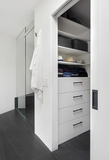 """""""Previously, the closet was not a walk-in and was stuffed head to toe with clothes,"""" says Wise. """"We carved out space from the hallway and created a walk-in that was outfitted from top-to-bottom with functional storage."""" A pocket door hides the interior when needed. The shower is in the same space as before, but lengthened so that Wise could use the awkward angled wall for a shower bench."""