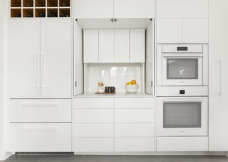 Full-height cabinetry, custom-built with a white matte lacquer finish, maxes out every square inch. The appliance garage at the center hides the Vitamix and coffee maker. When closed up, this bank of cabinets reads as a single wall and the finish reflects light, helping the space to feel bigger.