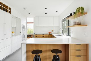 "Wise maintained the footprint of the kitchen, which is roughly 125 square feet, then maxed out the storage. ""Our goal here was to create a sleek and minimal kitchen respectful to the era of the home that was hyper-functional in a small space,"" says Wise. The black stools are from IKEA."
