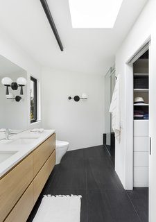"Now, a skylight fills the space with natural light. Large-format floor tile from Anne Sacks anchors the room while ""the rear wall of the bathroom and entire shower is wrapped in a beautiful, subtle plaster,"" says Wise. The sculptural sconce on the back wall, a focal point, is from Rejuvenation."