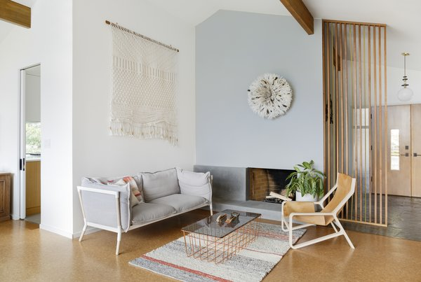A macramé wall hanging serves as large-scale, textural artwork in this sitting room.