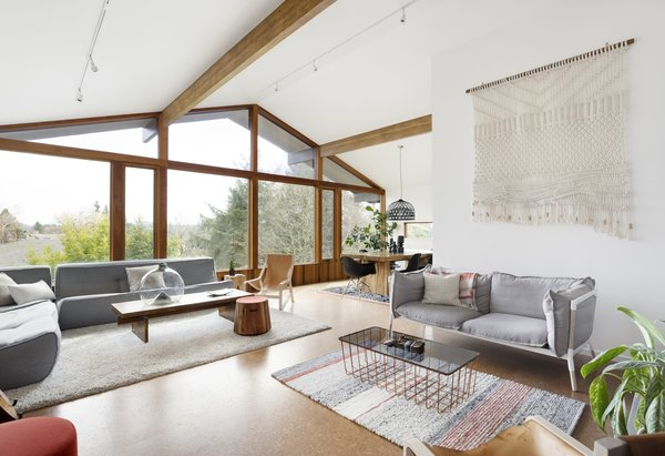When the homeowners of this 1960 home in Portland's Southwest Hills bought the property in 2009, they became the new owners of a lot of white carpeting, tired woodwork, dated wallpaper, and lackluster storage. Over time, they came to wish for a home that better suited their lives, but didn't want to sacrifice the excellent midcentury bones. A two-pronged renovation became the answer to their problems. For the first phase completed in 2016, Fieldwork Design + Architecture remodeled the main floor. The firm swapped out the white carpeting for warm cork flooring, then strategically inserted variegated cedar planking. Fireplace surrounds received new plaster to bring in a subtle, earthy texture. Sharp black accents, whether via dining chairs or new patio doors, add definition. Fieldwork replaced the trim around the windows with CVG fir and added variegated cedar planking for warmth and texture. For the second phase of the transformation, which wrapped in 2019, Annie Wise of Annie Wise Design stepped in for a gut remodel of the kitchen and master bathroom, with the goal of ensuring any changes remained consistent with what had already been done.