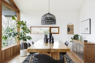 The mirror was replaced with a long window. The buffet moved with the owner from her childhood home. Black Eames chairs surround a generous wood table sourced by Annie Wise.