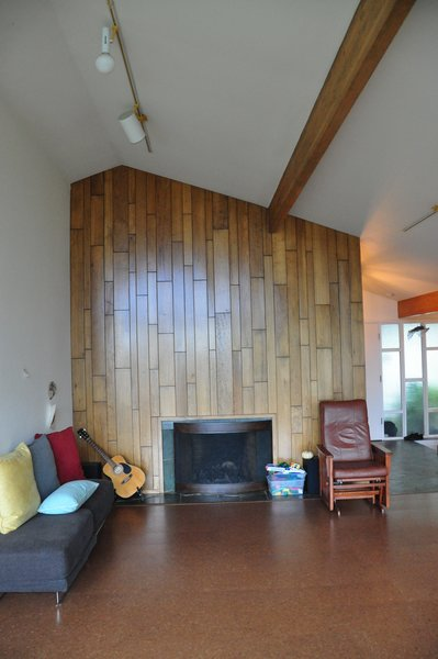 Before: this partial wall separates the living room from the entry. The cork flooring had already been installed, but the wood cladding around the fireplace needed updating.