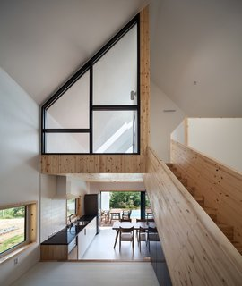 Wood cladding encases the ceiling of the kitchen at the lower level, covers the stairs, and defines the bedroom on the upper floor.