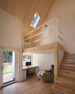A bedroom with a built-in work space and a raised platform.