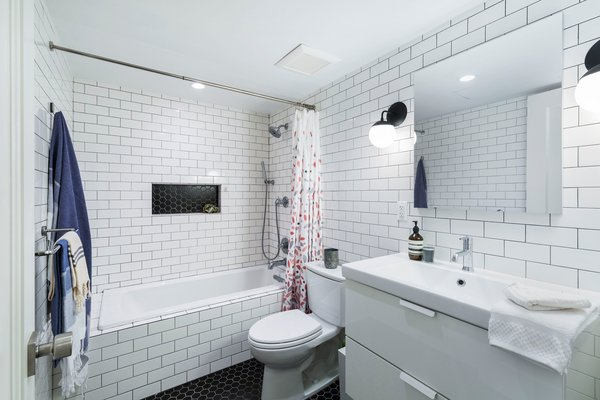 A classic scheme in the apartment bathroom utilizes white subway tile and two-inch black hex tile, both from Nemo. The vanity was sourced from IKEA, and a Cedar & Moss sconces flank the mirror.