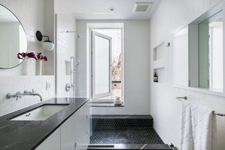 Now, a generous shower has a custom step-through window from Starr Windows & Doors to access the roof deck. Floors are Nero Marquina hexagon tile, and the custom vanity has a marble counter. A Kohler Purist faucet and Cedar & Moss sconce complete the look.