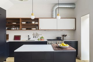 The kitchen was a collaboration between Urban Pioneering Architecture, Alex Scott Porter A+D, MW Construction, and CNS Construction. The lower cabinetry boxes are IKEA units with custom fronts and panels painted in Benjamin Moore Midnight Dream by MW Construction, while the upper floating walnut cabinet is custom. A Carrara marble counter syncs with the backsplash, which is Boneyard Brick from Chelsea Arts Tile & Stone. The pendant lights are the Mass Light NA5 from Norm Architects for &Tradition.