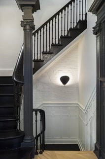 Now, the stairs and railing are painted Pitch Black from Farrow & Ball and a Gubi Cobra wall sconce illuminates the way.