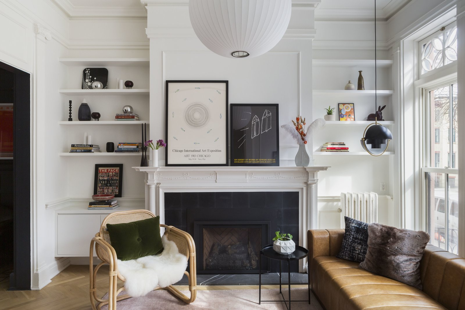 Custom shelving now flanks the fireplace, now composed of encaustic tile from the Cement Tile Shop and a marble hearth. A floating cabinet on one side balances an uncovered radiator on the other, and Benjamin Moore's Chantilly Lace unifies the scheme. Throughout the first floor, Bona Traffic white oak floors with a matte finish is laid in a herringbone pattern.